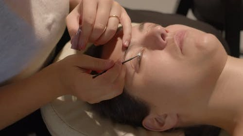 Beauty Therapist Applies a Fixing Product to Eye Lashes of Caucasian Woman for Lamination Procedure