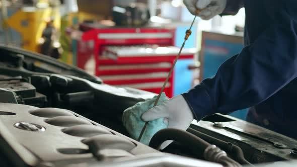 Automotive Technician Checks Engine Oil
