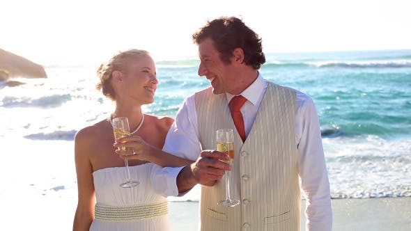 Thumbnail for Newlyweds Drinking Champagne On The Beach