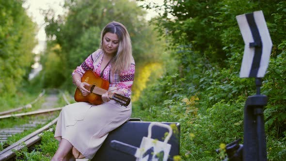 Thumbnail for Beautiful Woman Playing on Guitar and Sitting on Suitcase on Railway. Musician Woman Playing Guitar