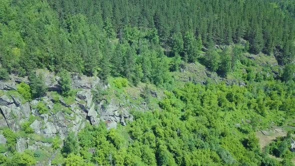 Thumbnail for Aerial: Flying Over Rocks and Pine Forest