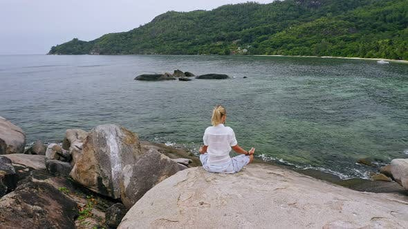 Thumbnail for Aerial Circling Footage of Blonde Girl Sitting in Yoga Pose on Granite Rock Surrounded By Exotic