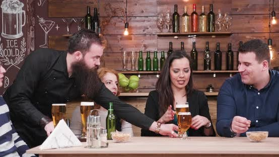 Bearded Hipster Waiter Serves Customers with Beer