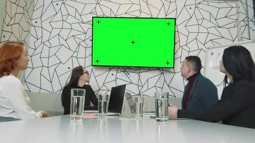 A Team of Business People in a Conference Room Watching a Picture on a TV Screen