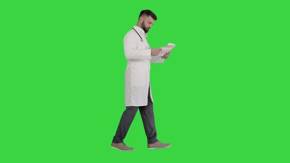 Male Doctor Walking and Looking at Cardiogram on a Green Screen, Chroma Key.