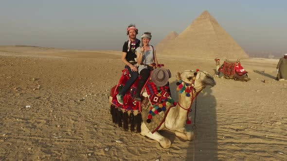 Smiling couple sitting on camel in front of Giza pyramids