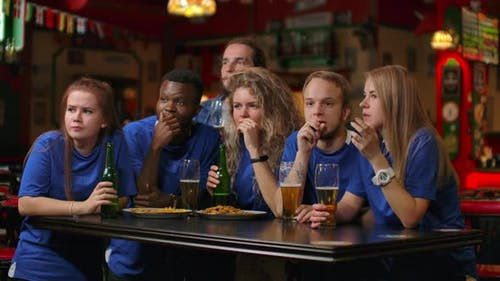 A Multiethnic Group of Friends of Fans in Blue Tshirts Will Watch a Match on TV in a Bar Watch a