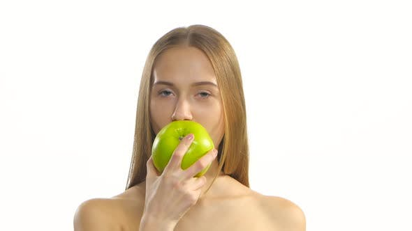 Thumbnail for Young Blonde Model Eating a Big Green Apple and Smile. White. Closeup