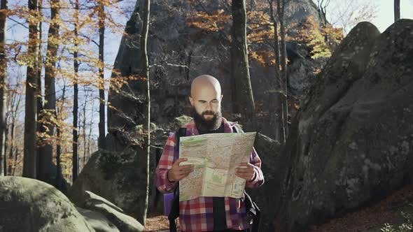 Handsoome Man Wearing a Beard Keeps a Tourist Map in His Hands