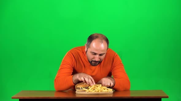 Thumbnail for Caucasian Man with Overweight Looks at Delicious Junk Foods on the Table Then Playing with French