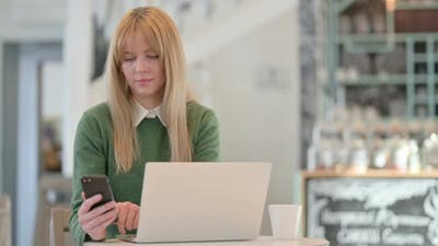 Young Woman Working on Smartphone and Laptop in Cafe in Cafe