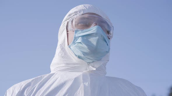 Thumbnail for Close-up Portrait of Young Caucasian Man in White Safety Suit and Protective Eyeglasses at the