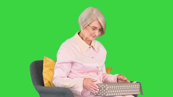 Senior Woman Sitting in Comfortable Armchair and Opening a Present on a Green Screen Chroma Key