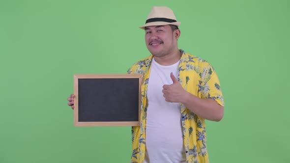 Thumbnail for Happy Young Overweight Asian Tourist Man Holding Blackboard and Giving Thumbs Up