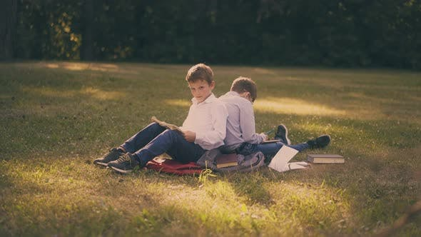 Schoolboys with Books Prepare for Exams on Grass in Park