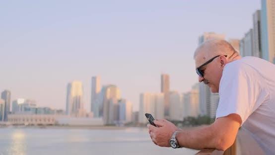 Thumbnail for Mature Senior Man Walking Texting on Cell Phone