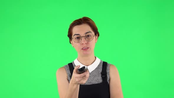 Thumbnail for Portrait of Funny Girl in Round Glasses with TV Remote in Her Hand, Switching on TV, Green Screen