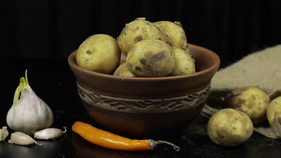 Thumbnail for Dirty Raw Potatoes on a Plate on Table with Garlic and Pepper