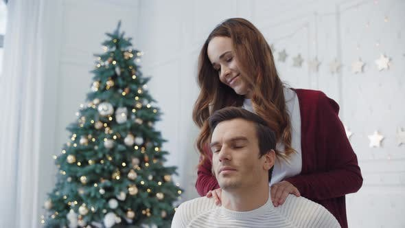 Closeup Flirting Wife Massaging Husband in Christmas Decorated Room