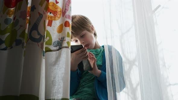 Thumbnail for Kleiner Junge spielen Video spiele mit Smartphone.