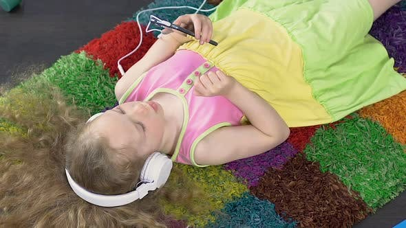 Thumbnail for Charming Daughter Listening To Music In Large White Headphones, Technology