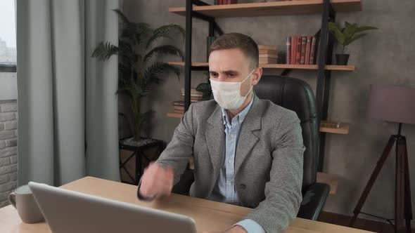 Thumbnail for Young Businessman Sneezes Into Protective Face Mask Working in the Office. Caucasian Man with Acute
