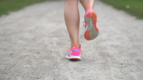Legs of a Woman Runner Running Along the Road in a Summer Day, Close-up