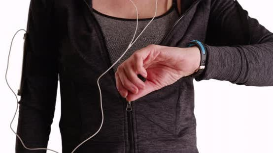 Thumbnail for Close up of female jogger using smart watch to track run on white background