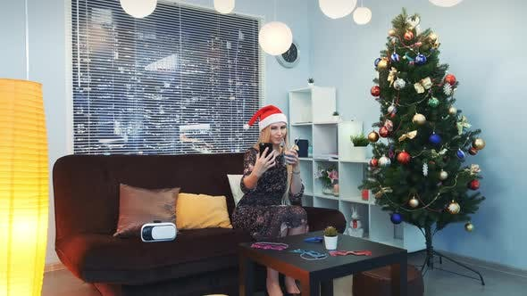Thumbnail for Attractive Young Lady Making Selfie in Santa Hat and with Drink in Her Hands