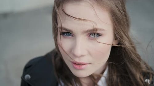 Closeup Portrait of a Beautiful Girl with Bright Blue Eyes. Hipster Looking at Camera