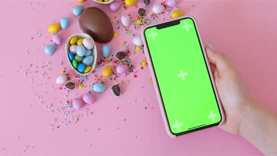 Thumbnail for Woman hand holding Iphone Xs with keyed green screen On Pink Background Over Easter Eggs And Candy
