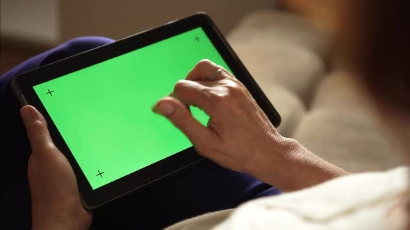 Thumbnail for Elderly woman using a digital tablet PC with green screen, back view