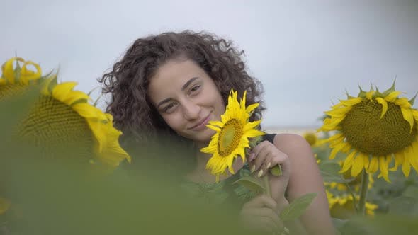 Thumbnail for Portrait of Lovely Fun Curly Playful Sensual Woman Looking at the Camera Smiling Standing on
