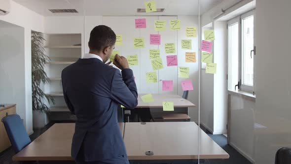 Thumbnail for Back View of Businessman Writing on Sticky Memos