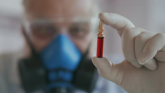 Thumbnail for Extreme Close-up of a Scientist in a Blue Respirator and Protective Glasses, a Developer