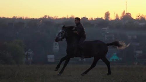 Kerl bei Sonnenuntergang springen auf einem Hengst