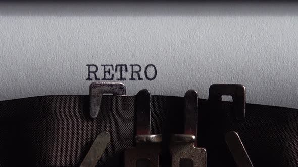 Typing word Retro on a vintage typewriter. Close up.