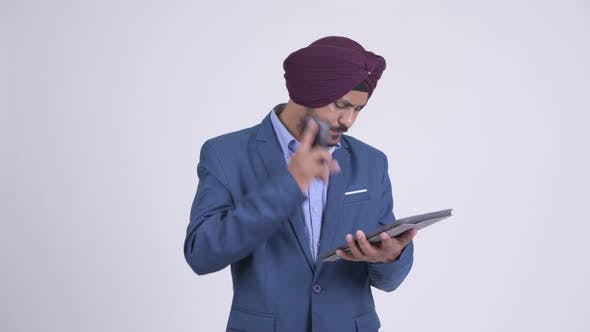 Thumbnail for Bearded Indian Sikh Businessman Talking on Phone and Using Digital Tablet