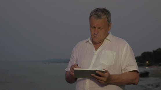 Man typing on tablet while standing on beach