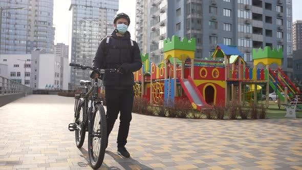 Delivery Man in Medical Mask Walking with Bicycle