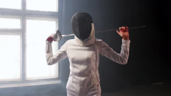 Thumbnail for A Young Woman Fencer with a Helmet Putting the Sword Behind Her Shoulders in the Studio