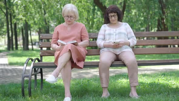 Wide Shot Portrait of Two Senior Women Enjoying Hobbies on Bench in Sunny Park. Absorbed Caucasian