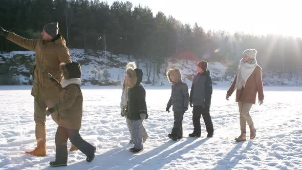 Thumbnail for Young Family Walking Together in Snow