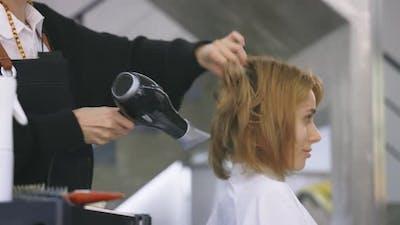 Hairdresser Using Hairdryer on Client Hair