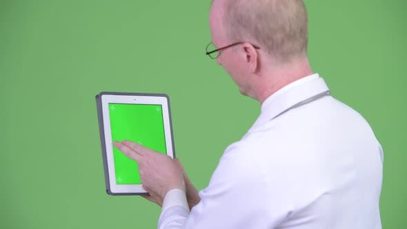 Thumbnail for Rear View of Mature Bald Man Doctor Using Digital Tablet
