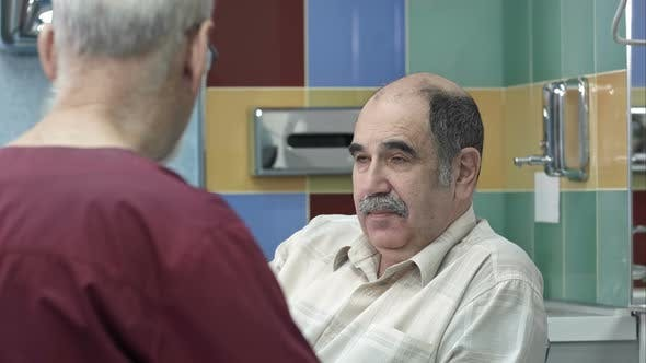 Senior männlicher Arzt im Gespräch mit Senior Mann in Chirurgie