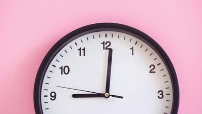 Black Clock on Pink Background Close Up