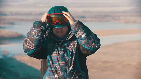 Thumbnail for Man Snowboarder in Helmet Putting on Protective Glasses