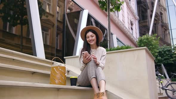 Smiling Young Lady in Modern Clothes and Trendy Hat Sitting on Steps Near Urban Buildings