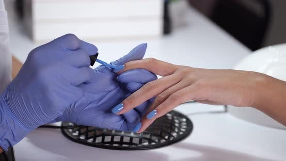 Thumbnail for Close-up of Beautician Hands Making Blue Manicure for Client